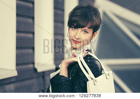 Happy young fashion woman with handbag on city street. Female fashion model in leather jacket outdoor