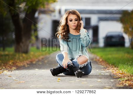 Sad young fashion woman sitting on city street. Female fashion model with long curly hairs in ripped jeans outdoor