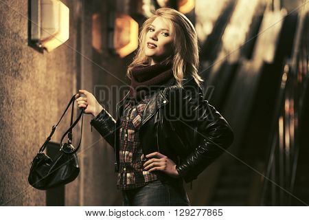 Young fashion blond woman with handbag. Female fashion model in black leather jacket