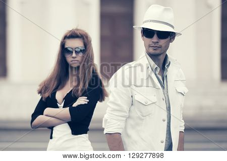 Young couple in conflict on city street. Male and female fashion model in sunglasses.  Young man and woman outdoor