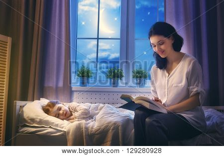 Family reading bedtime. Pretty young mother reading a book to her daughter.