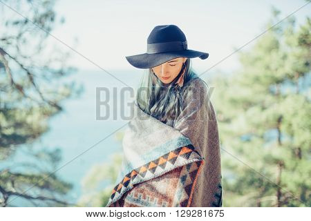 Beautiful girl wearing in poncho and hat walking in summer forest on background of sea