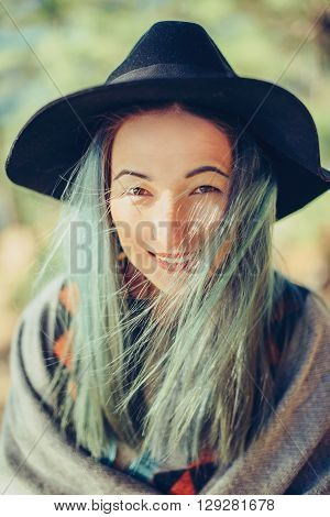 Outdoor portrait of smiling young woman in hat and poncho woman looking at camera