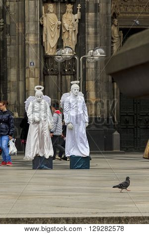 Cologne, Germany - May 16 2013: These are sculptures of saints on the facade of the cathedral living sculptures of angels near the entrance to the cathedral and a dove came down to them from heaven May 16, 2015 in Cologne, Germany.