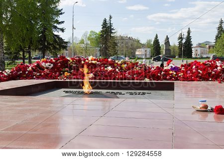 PETROZAVODSK, RUSSIA - MAY 10TH, 2016: Eternal fire against carnation flowers after May 9th day of great victory, celebration of the victory in the second world war