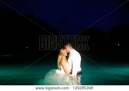 Bride And Groom Posing In Water At Night