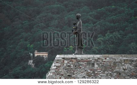 view in profile on Statue of Our Lady (the Virgin Mary and baby Jesus) in Budapest with green hill on the background