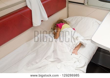 A Child In A Train Sleeping Wrapped In A Sheet In The Lower Place In The Second-class Compartment Wa