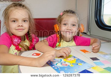 Two Little Sisters In The Train Of Fun Playing At The Table At The Lower Place In The Second-class C