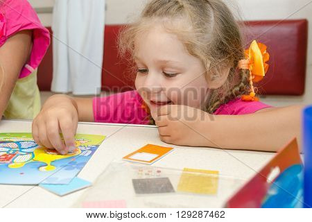 Four-year Girl On A Train Sitting At The Table On The Lower Second-class Place Car And Enthusiastica