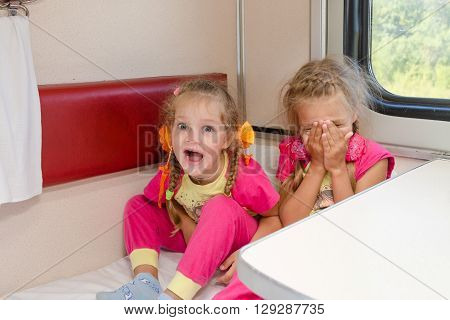 Two Cheerful Little Girls Are Sitting On The Train On The Lower Second-class Place Car In The Same P