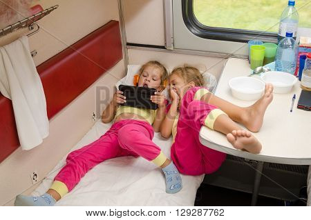 Two Little Girls Lie On The Train With His Feet On The Lower Second-class Place Car In The Same Paja
