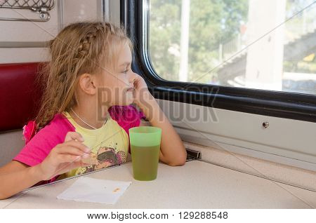 Six-year Girl Sitting On The Train At The Table On Outboard Second-class Carriage And Enthusiastical