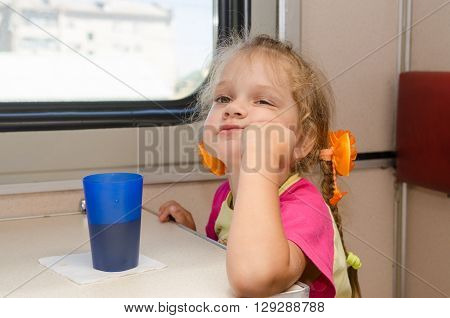 A Girl Of Four Years Of Thoughtful And Tired Of Sitting On The Train At The Table On The Side A Plac