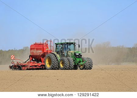SALO, FINLAND - MAY 8, 2016: John Deere 6125R agricultural tractor and Horsch seed drill on dusty field at spring with blue sky.