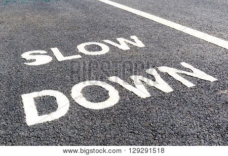 Close up slow down marking on street for warning the drivers to reduce speed.