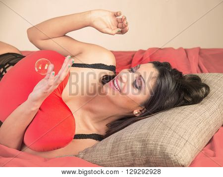 beautiful brunette posing on red sofa with red pillow