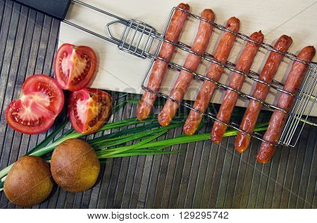 grill-grate for sausages on a wooden cutting board and tomato bread onions on a brown wooden striped background