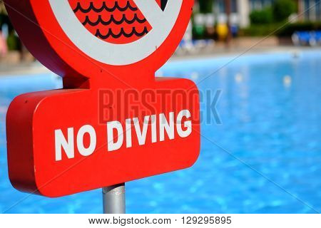 Red no diving warning sign at the poolside. Selective focus