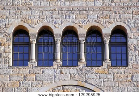 five old windows with arches columns and lattices on a stone brown wall