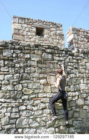 Belgrade, Serbia - April, 23, 2016: Girl practicing free climbing on the walls of Belgrade medieval fortress Kalemegdan