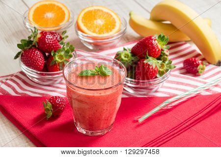 Fruit smoothie glass on red and white stripes napkins around spread ingredients: strawberries sliced orange bananas blurred on white wood background. Horizontal. Daylight.