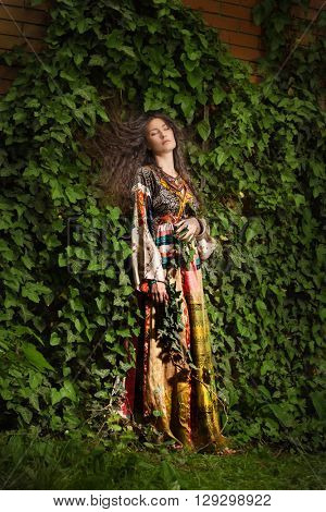 beautiful young woman in long dress in garden lean on ivy full body shot