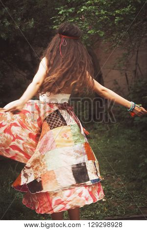 young woman in bohemian style clothes dance in garden