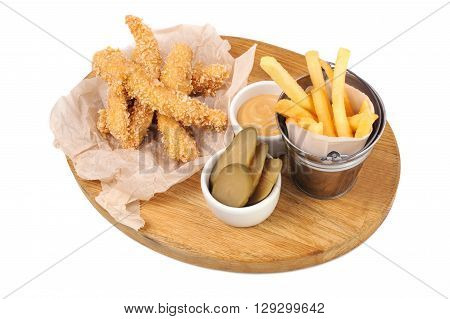 fried chicken strips with french fries and sauce on wood board