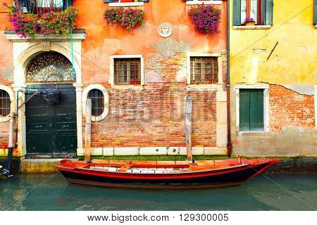 Boat near old house on narrow canal in Venice