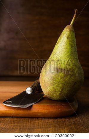 Pear and chopper on wooden cutting board