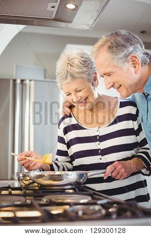 Happy senior man standing with wife cooking food at hob in kitchen