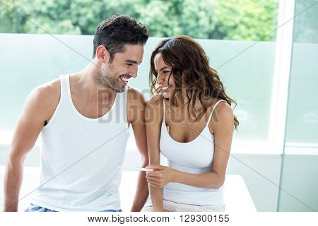 Happy woman holding pregnancy kit while sitting beside husband at home