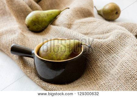 Three pears: one in clay pot two on the jute bag