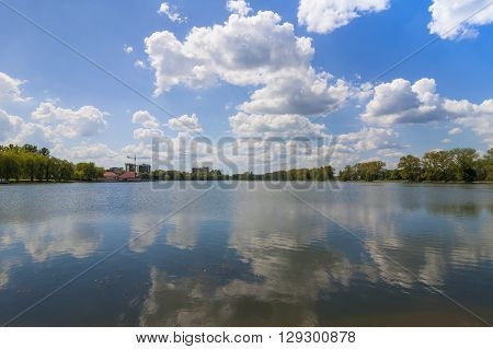 Clear lake reflecting blue sky with puffy white clouds in bright sunny day
