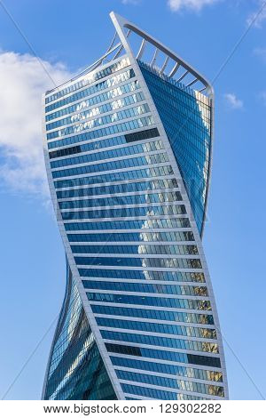 Moscow, Russia - April 23, 2016: Header of the Evolution Tower in the business complex Moscow City with blue sky and reflection of city and clouds in mirrors