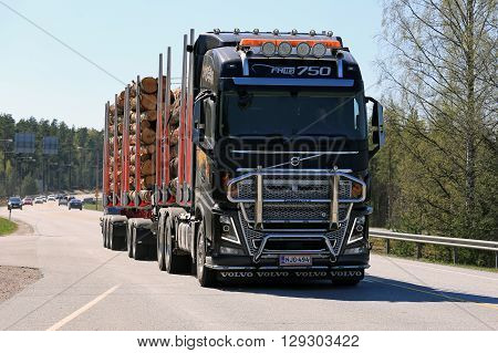 NUMMELA FINLAND - MAY 5 2016: Black Volvo FH16 750 logging truck hauls timber along highway in South of Finland at spring.