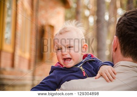 Baby boy crying on his father shoulder, copy space