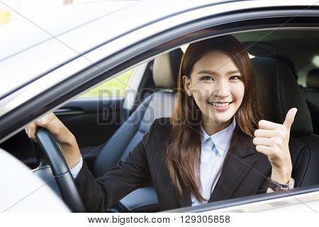 young business woman sitting in car and showing thumbs up