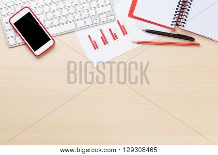 Office desk workplace with charts, pc, smartphone and notepad on wooden table. Top view with copy space