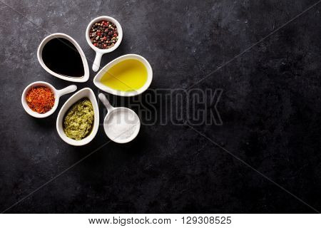 Condiments and spices on stone background. Top view with copy space