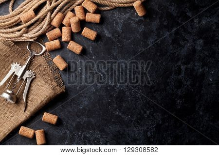 Wine corks and corkscrew over dark stone background. Top view with copy space