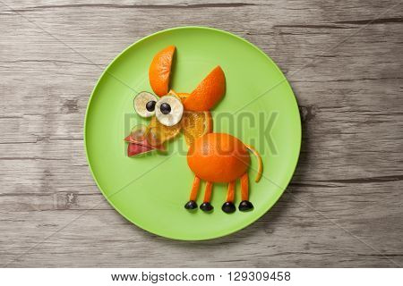 Donkey made of juicy fruits on plate and wood