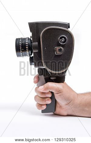 Hand Holding A Vintage Movie Camera Isolated On White