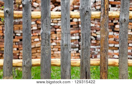Rustic wooden fence with a cabin or rural cottage wall visible beyond and a green lawn area.
