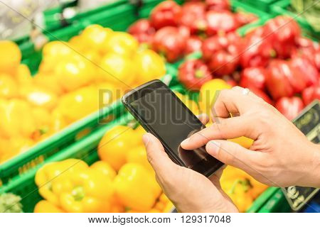 Man hand digiting on mobile smart phone touchscreen - Online shopping concept with electronic products purchase through smartphone dedicated app - Modern lifestyle with technology in everyday life