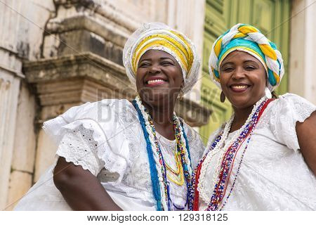 Brazilian women of African descent wearing traditional clothes from the state of Bahia in the old colonial district of Salvador (Pelourinho)