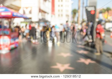 Abstract defocused bokeh view of artist stars and everyday multiracial people around the world famous Walk Of Fame in late afternoon on Hollywood Boulevard in LA California - United States of America
