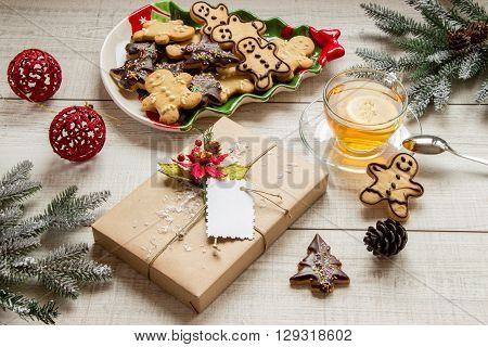 New Year's gift right cup of lemon tea in the background Christmas cookies on plate Christmas tree branche on a white wood. Horizontal. Close.