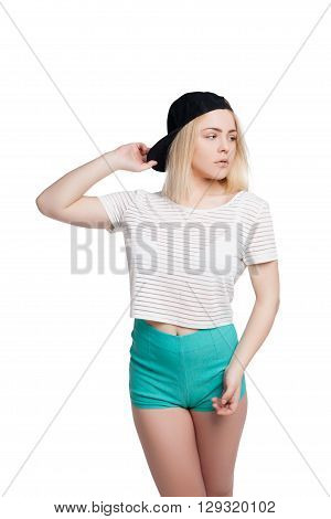 Pretty young woman wearing green shorts, striped tshirt and cap posing isolated on white background